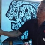 Fajar Iriadi sedang menyelesaikan lukisan hitam-putih di kanvas berukuran 2x1,5 meter. (Foto: Agus Hidayat)