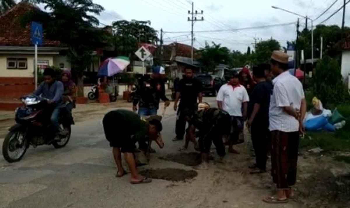 aksi tambal sulan jalan Raya Ambunten Sumenep oleh pemuda GP Ansor setempat