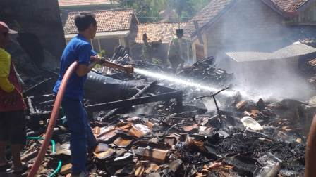 Proses pembasahan api di lokasi kebakaran kandang sapi dan dapur (Foto. Rafi @portalmadura.com)
